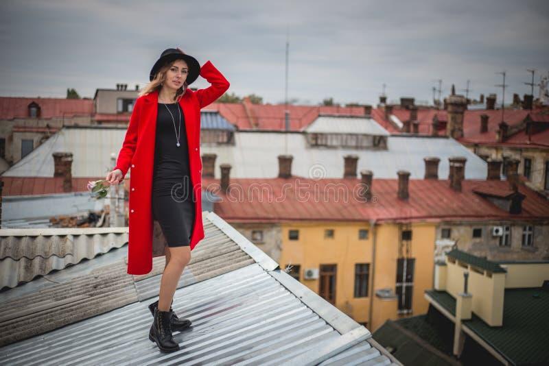 Ragazza nel rosso e con la posa black hat sul tetto di vecchia città immagine stock