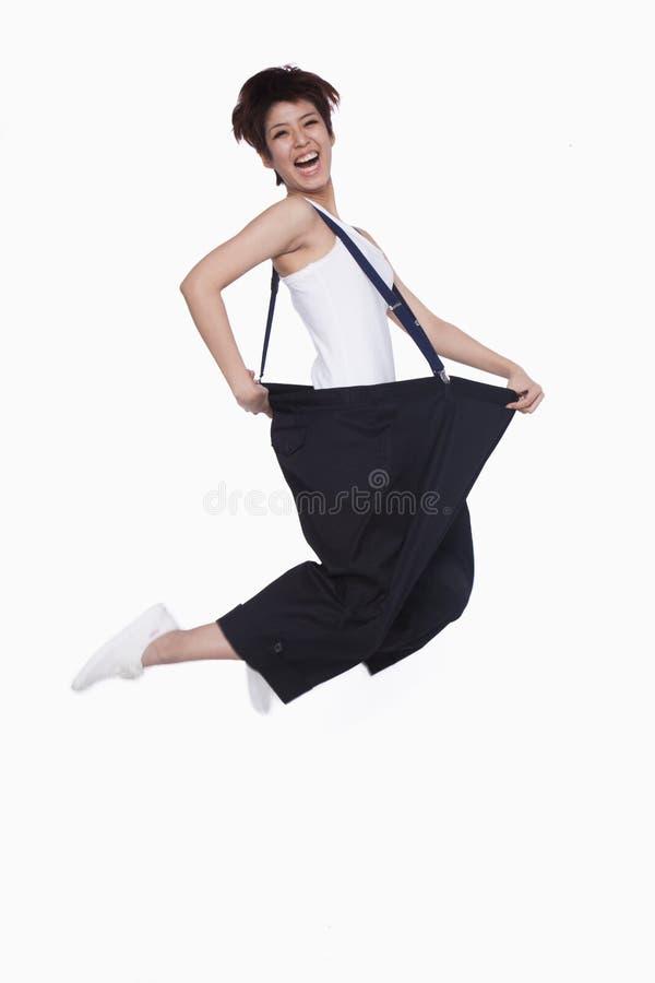 Ragazza nel salto surdimensionato dei pantaloni immagini stock