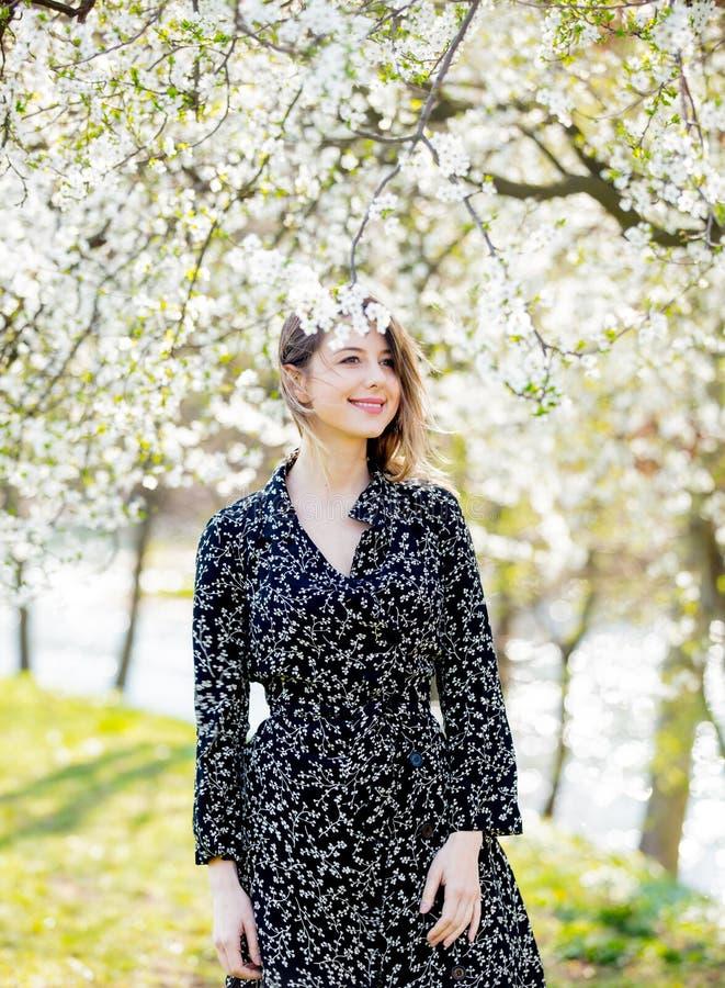 Ragazza nel soggiorno scuro del vestito vicino ad un albero di fioritura fotografia stock libera da diritti