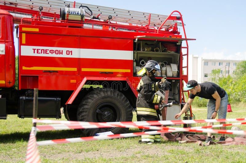 Ragazza nel vestito del ` s del vigile del fuoco contro un'autopompa antincendio che prepara al overc fotografia stock libera da diritti