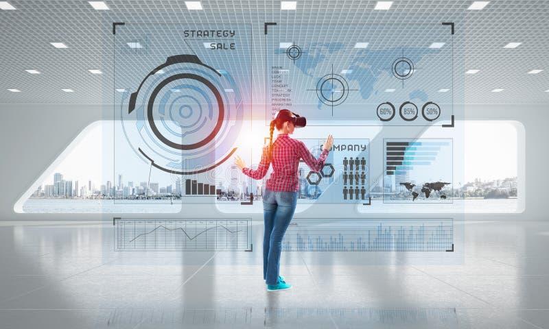 Ragazza nell'interno dell'ufficio nella maschera di realtà virtuale facendo uso delle tecnologie innovarici Media misti immagini stock
