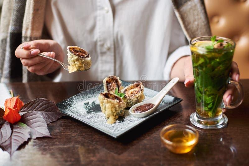 Ragazza nella bevanda di tenuta bianca che mangia il rotolo di sushi dolce immagini stock