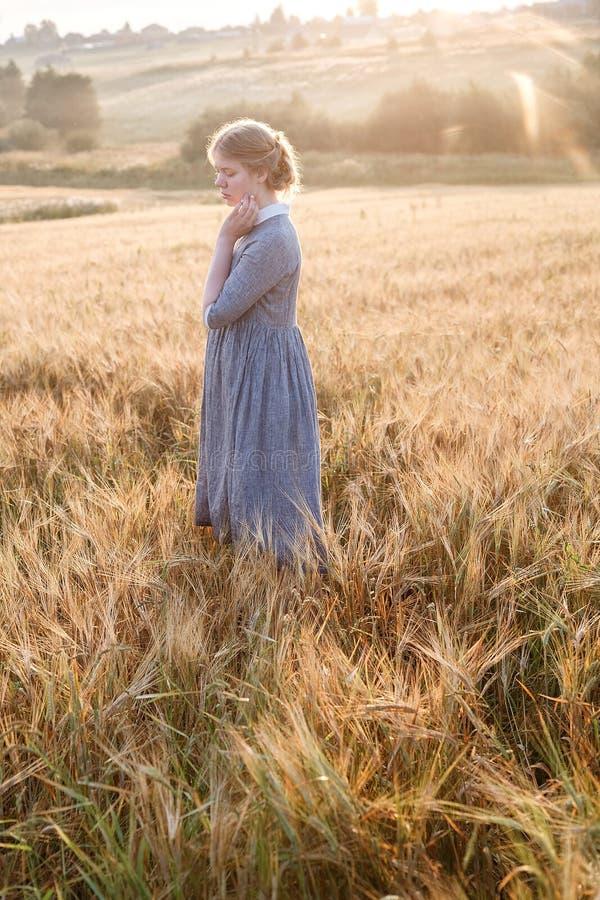 Ragazza nella condizione blu del vestito all'alba nel campo delle orecchie alla luce dorata del sole paesaggio del paese e della  fotografia stock libera da diritti