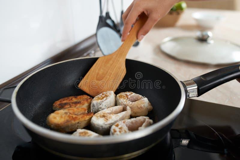 Ragazza nella pentola del pesce della frittura della cucina fotografia stock