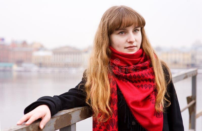Ragazza nella sciarpa rossa e nel cappotto nero fotografia stock