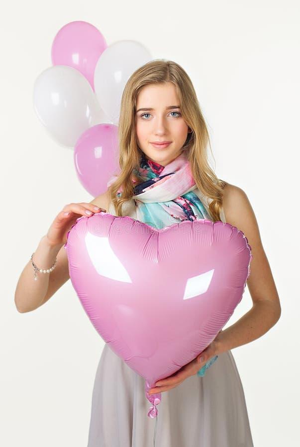Ragazza nello sguardo di primavera con il cuore rosa del baloon Giorno del biglietto di S immagini stock libere da diritti