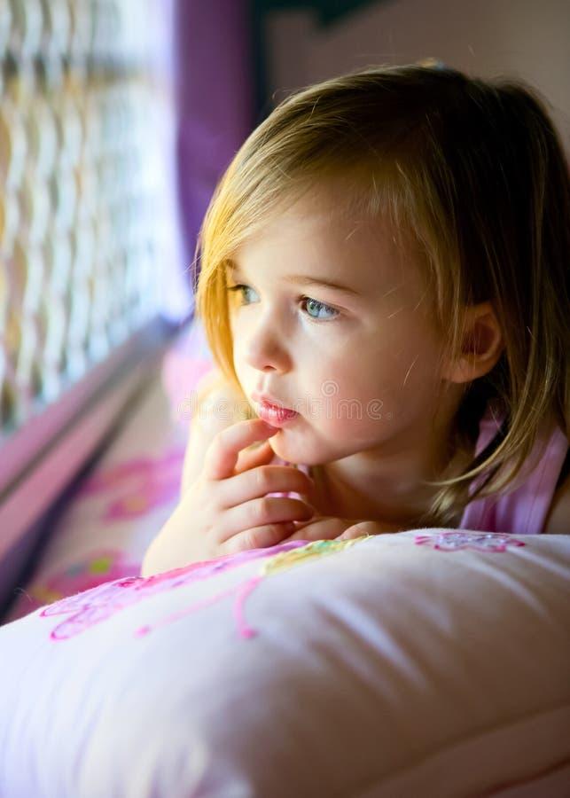 Ragazza nello sguardo fuori della sua finestra della camera da letto fotografia stock libera da diritti
