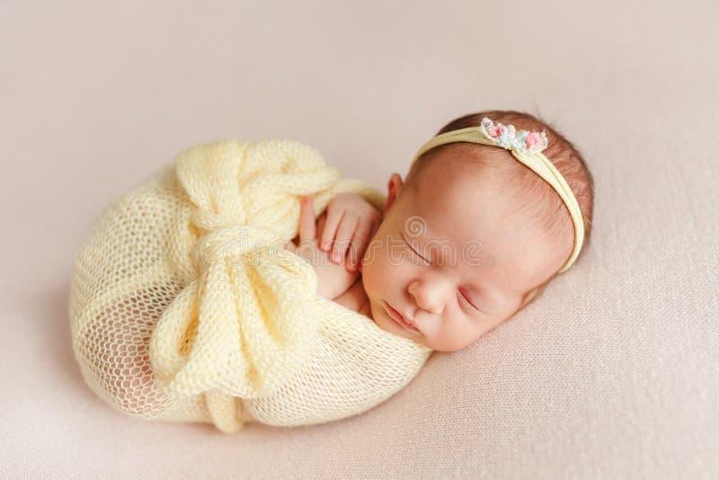 Ragazza neonata addormentata sveglia con una fasciatura sulla sua testa avvolta dentro fotografie stock