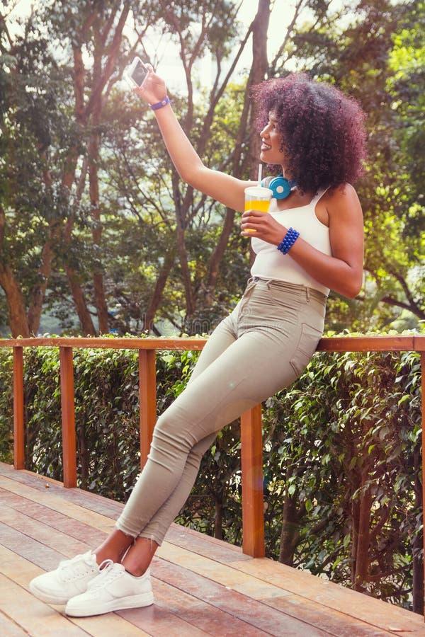 Ragazza nera che prende una fotografia del selfie e una tazza di succo per il socia fotografie stock libere da diritti