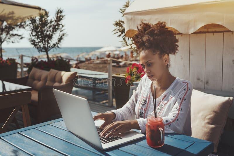 Ragazza nera che utilizza computer portatile nel caffè vicino al mare fotografie stock