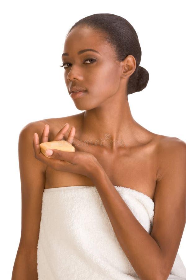 Ragazza nera con la barra del sapone in tovagliolo di bagno bianco fotografia stock libera da diritti