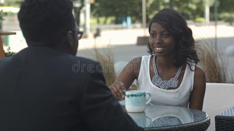 Ragazza nera con la tenuta della tazza di caffè, parlando con suo collega afroamericano, sedentesi fuori del caffè fotografia stock