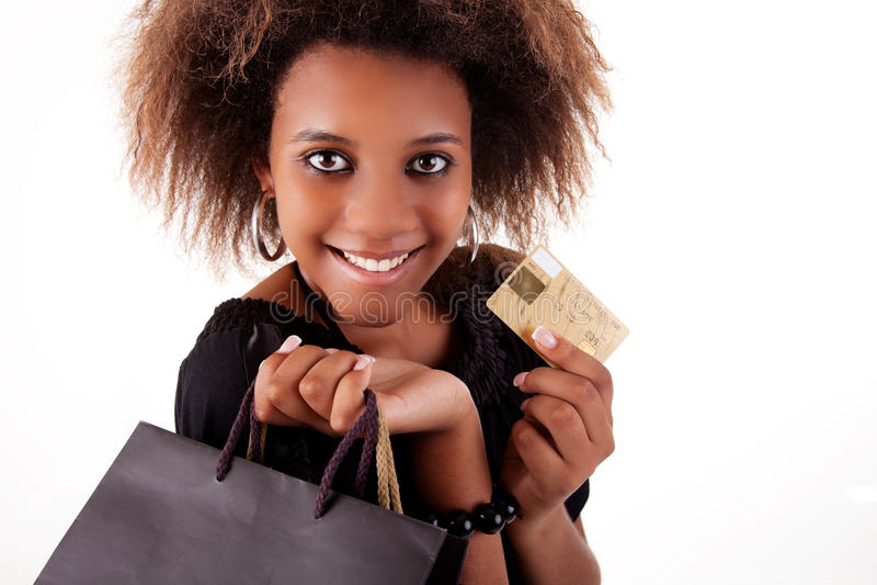 Ragazza nera felice con i sacchetti di acquisto, carta di credito fotografia stock