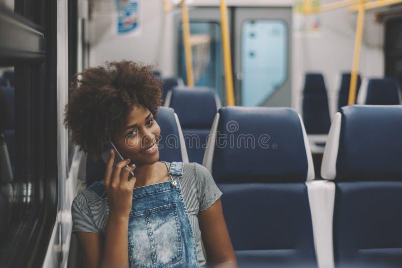Ragazza nera riccia sorridente in treno facendo uso dello Smart Phone immagine stock libera da diritti