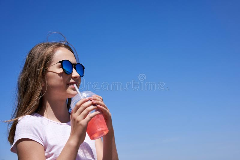 Ragazza in occhiali da sole che beve limonata fredda fotografia stock