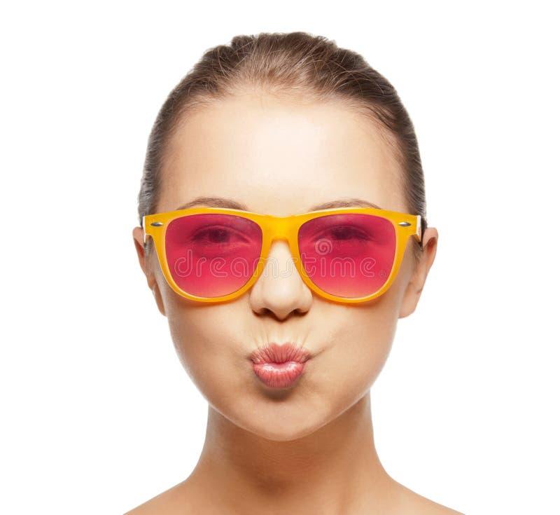 Ragazza in occhiali da sole rosa che soffiano bacio immagine stock libera da diritti