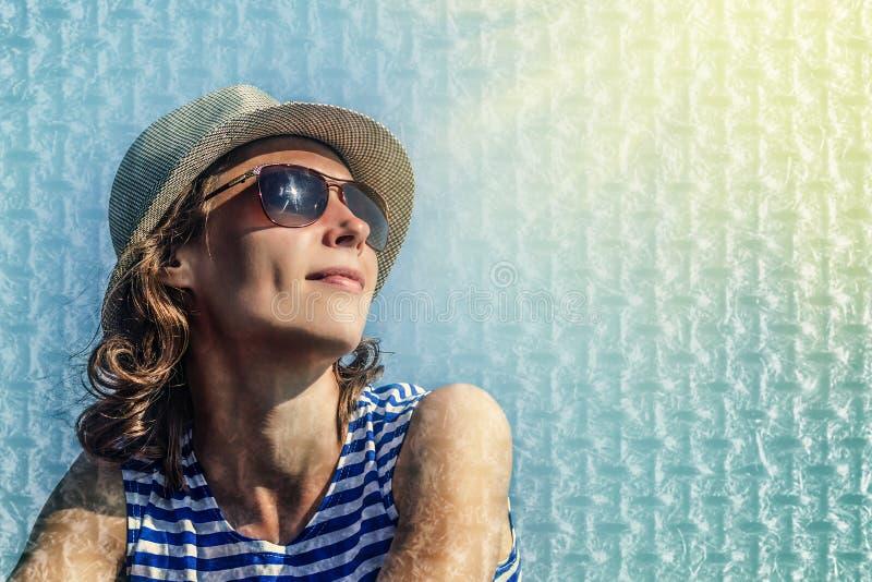 Ragazza in occhiali da sole su un fondo blu immagini stock libere da diritti