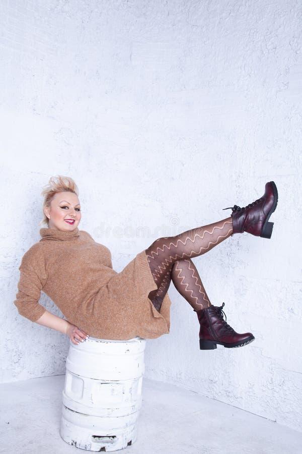 Ragazza paffuta sveglia con i capelli di scarsità in grandi maglione e collant marroni caldi su fondo bianco in studio fotografia stock libera da diritti