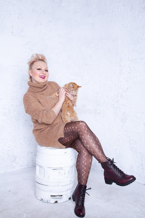 Ragazza paffuta sveglia con i capelli di scarsità in grandi maglione e collant marroni caldi su fondo bianco in studio immagine stock libera da diritti