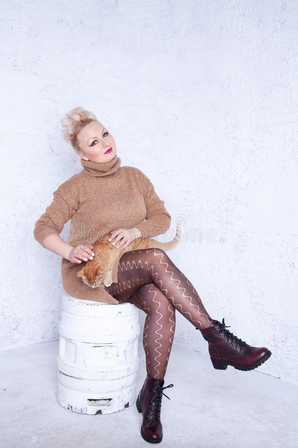 Ragazza paffuta sveglia con i capelli di scarsità in grandi maglione e collant marroni caldi su fondo bianco in studio fotografie stock libere da diritti