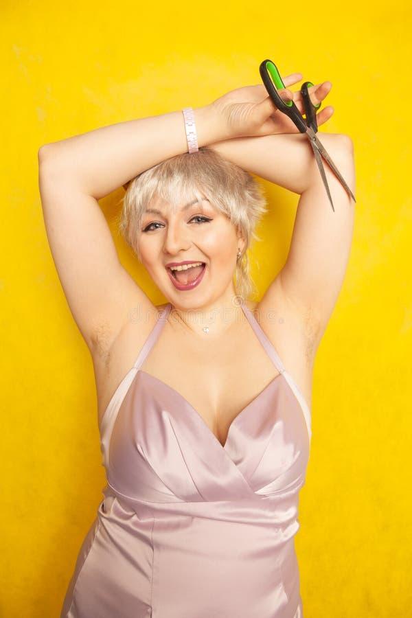 Ragazza paffuta in vestito con le ascelle pelose non rasate e le forbici a disposizione su fondo giallo in studio immagine stock libera da diritti