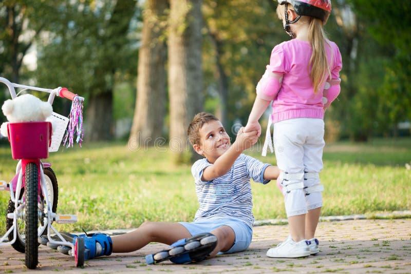 Ragazza in parco, ragazzo di aiuti con i pattini di rullo da stare su fotografia stock