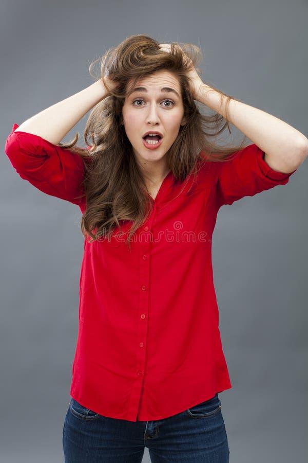 Ragazza pazza 20s che incasina i suoi capelli per la sorpresa immagini stock
