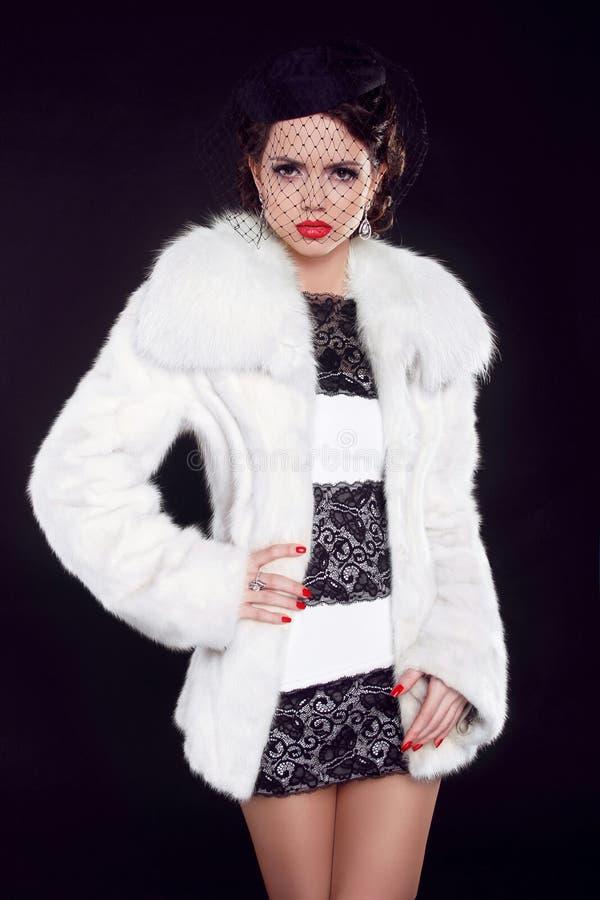 Ragazza in pelliccia di lusso, signora di inverno di modo isolata sulla b nera fotografia stock libera da diritti