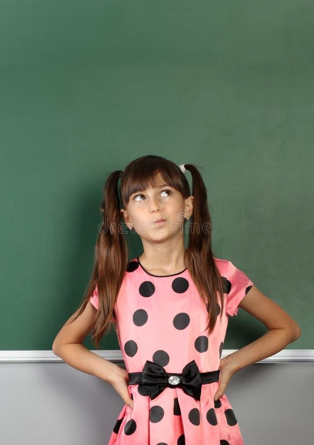 Ragazza pensierosa del bambino vicino alla lavagna in bianco della scuola immagini stock