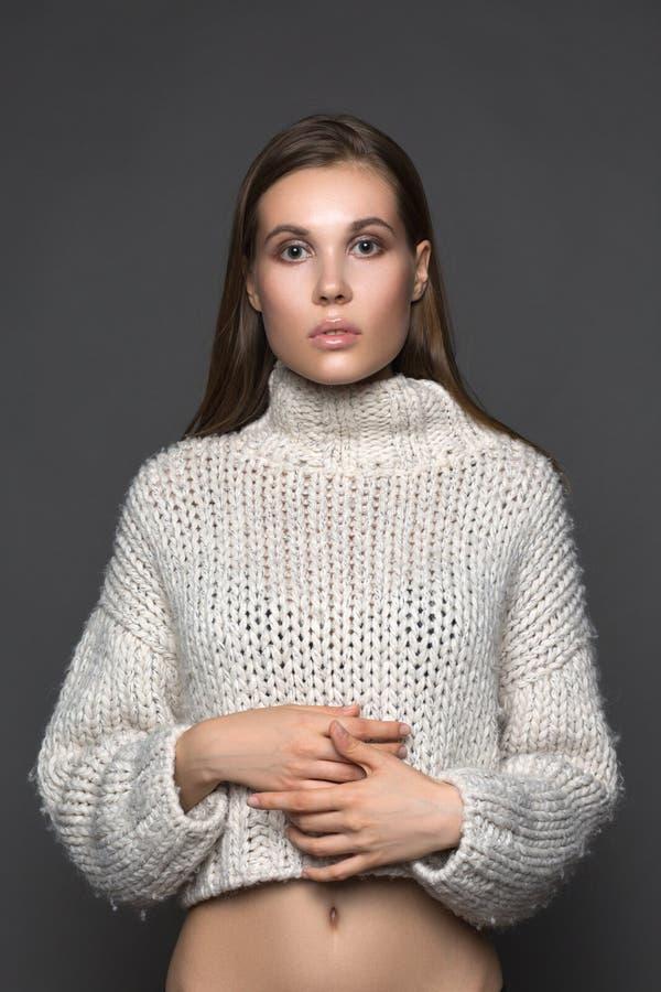 Ragazza perfetta nel modo e nella bellezza bianchi del primo piano del maglione fotografia stock