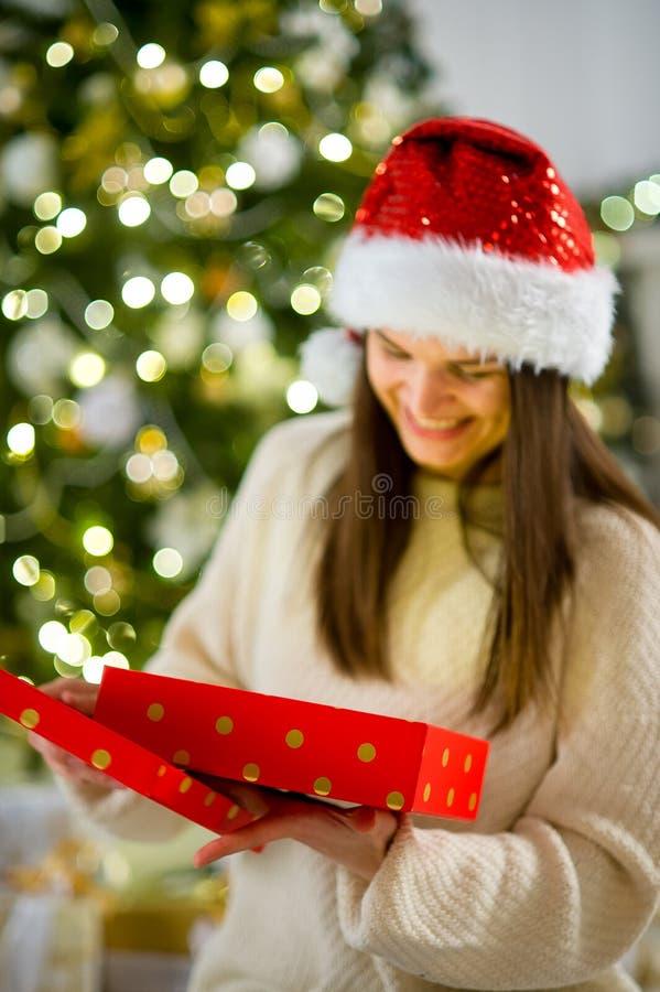 Ragazza piacevole l'apertura castana una scatola con il regalo di Natale fotografia stock libera da diritti