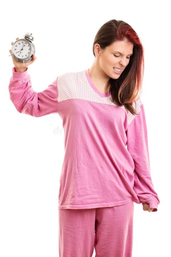Ragazza in pigiami che tengono una sveglia fotografia stock libera da diritti