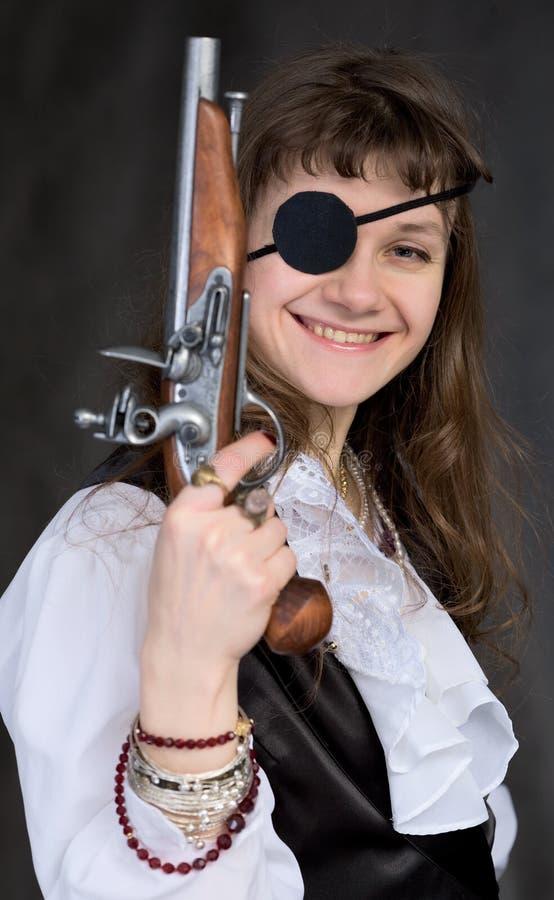 Ragazza - pirata con la pistola a disposizione e la zona dell'occhio fotografie stock