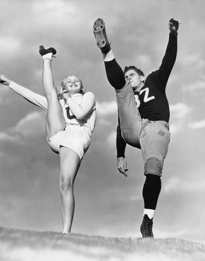 Ragazza pon pon e giocatore di football americano che danno dei calci nell'aria (tutte le persone rappresentate non sono vivente  fotografie stock