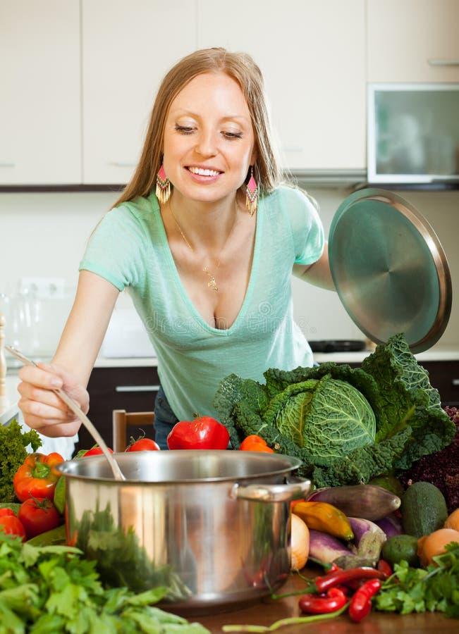 Ragazza positiva che cucina con la siviera dalle verdure fotografia stock libera da diritti