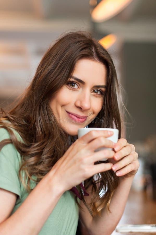 Ragazza positiva che prende una rottura che si siede alla barra nel negozio del caffè fotografie stock