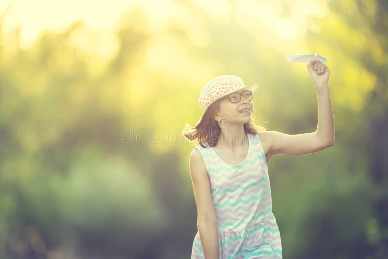 Ragazza pre-teenager allegra che gioca con l'aereo di carta sul parco all'alba Ragazza con i ganci dei denti e di vetro fotografie stock