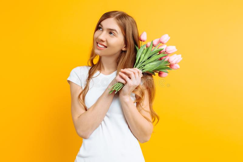 Ragazza premurosa felice, tenente un mazzo dei fiori a disposizione, su un fondo giallo fotografia stock