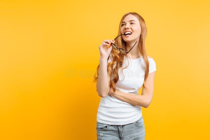 Ragazza premurosa positiva in vetri, nei sogni e nei piani qualcosa, su un fondo giallo immagini stock