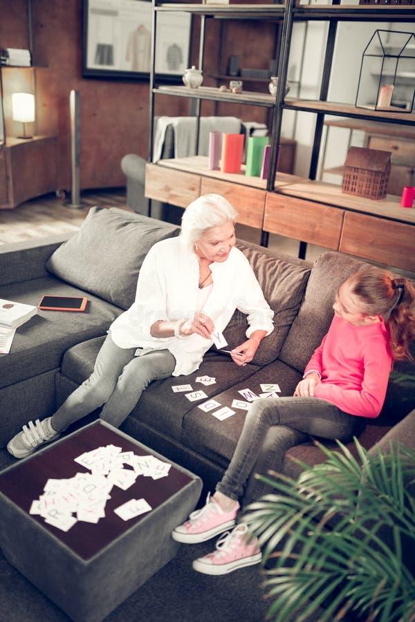 Ragazza prescolare che studia le lettere con sua nonna preoccupantesi fotografie stock