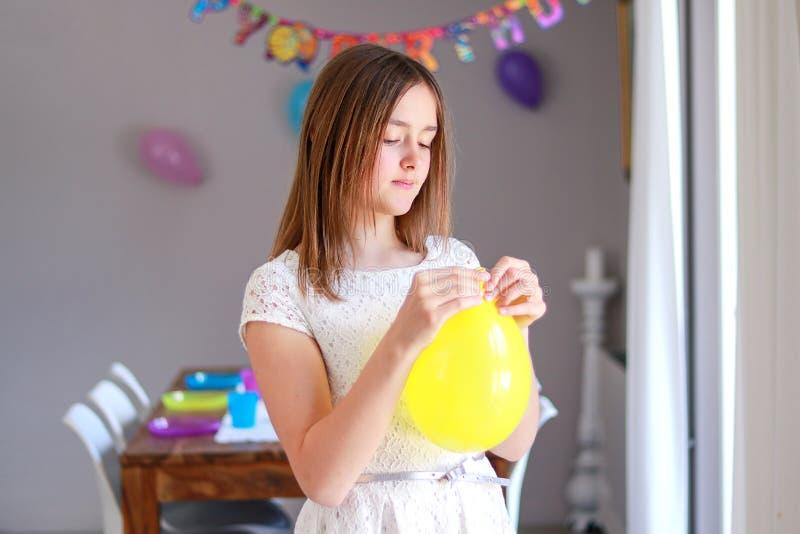 Ragazza preteen felice che soffia pallone giallo che decora casa che prepara alla festa di compleanno dei bambini fotografia stock