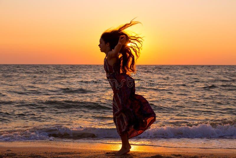 Ragazza pronta a saltare sulla costa di mare ad alba fotografia stock