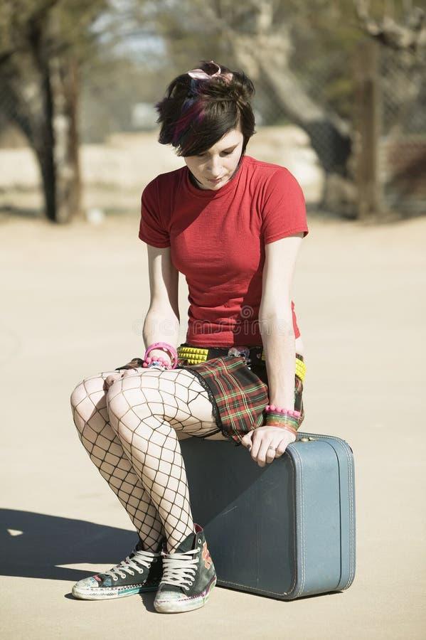 Ragazza punk che si siede sulla valigia immagini stock