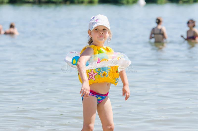 Ragazza quadriennale sulla spiaggia che indossa un giubbotto di salvataggio e un cerchio immagine stock libera da diritti
