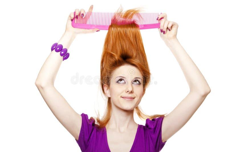 Ragazza red-haired divertente con il grande pettine. immagini stock