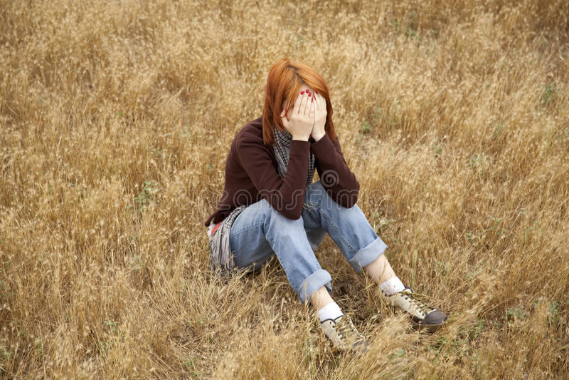 Ragazza red-haired triste sola al campo fotografia stock