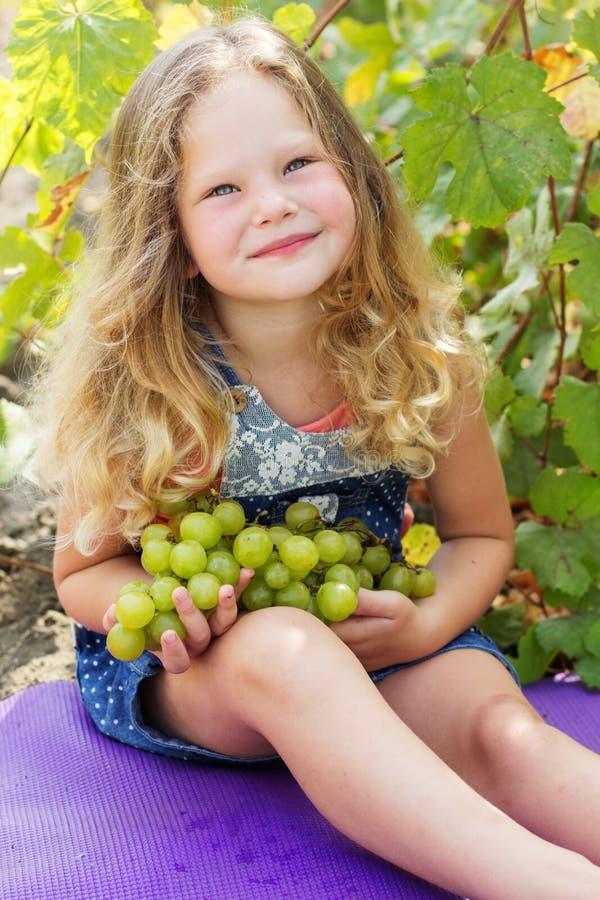 Ragazza riccia bionda del bambino con il mazzo di uva fotografia stock