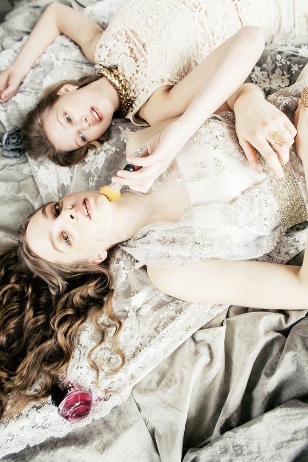 Ragazza riccia bionda dell'acconciatura della sorella gemellata graziosa due nell'interno di lusso della casa insieme, concetto r fotografie stock