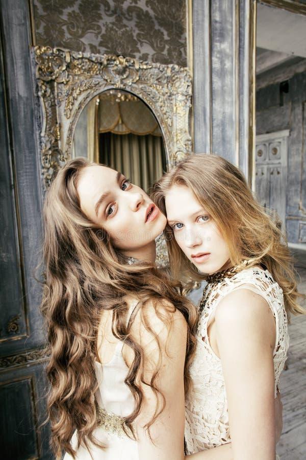 Ragazza riccia bionda dell'acconciatura della sorella gemellata graziosa due nell'interno di lusso della casa insieme, concetto r immagine stock libera da diritti