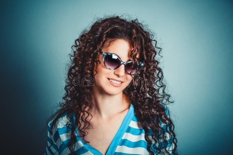 Ragazza riccia della donna nel sorridere degli occhiali da sole immagine stock libera da diritti